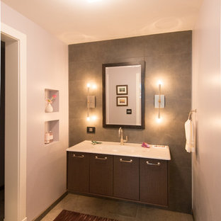Inspiration for a mid-sized contemporary 3/4 gray tile and stone tile bathroom remodel in Chicago with an integrated sink, flat-panel cabinets, dark wood cabinets, a one-piece toilet and gray walls