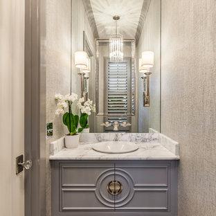 Неиссякаемый источник вдохновения для домашнего уюта: маленькая ванная комната в стиле современная классика с фасадами с декоративным кантом, серой плиткой, паркетным полом среднего тона, мраморной столешницей, коричневым полом, белой столешницей, серыми фасадами, плиткой из листового стекла, серыми стенами и врезной раковиной