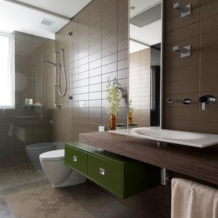 Foto di una stanza da bagno minimalista con lavabo a bacinella, ante lisce, ante verdi, top in legno, doccia a filo pavimento, piastrelle marroni, pareti marroni e top marrone