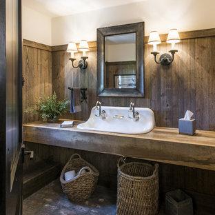 Modelo de cuarto de baño campestre, grande, con armarios abiertos, puertas de armario de madera oscura, suelo de ladrillo, lavabo de seno grande, encimera de madera, paredes marrones y encimeras marrones
