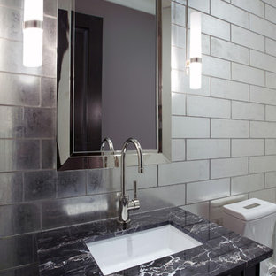 This is an example of a traditional bathroom in Chicago with a submerged sink, marble worktops and glass tiles.