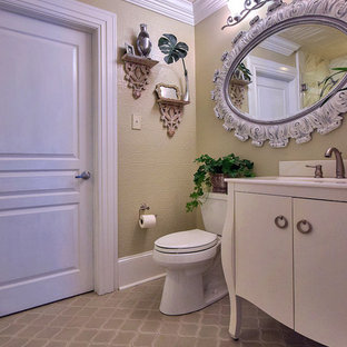 Inspiration for a mid-sized shabby-chic style 3/4 white tile and ceramic tile ceramic floor and brown floor alcove shower remodel in New Orleans with a drop-in sink, furniture-like cabinets, white cabinets, beige walls, a two-piece toilet, a hinged shower door and solid surface countertops