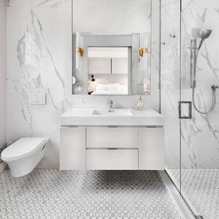 Imagen de cuarto de baño actual con armarios con paneles lisos, puertas de armario blancas, ducha empotrada, sanitario de pared, baldosas y/o azulejos blancos, paredes púrpuras, lavabo integrado, suelo gris y encimeras blancas