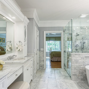 Inspiration for a timeless master marble tile marble floor and gray floor bathroom remodel in Columbus with beaded inset cabinets, white cabinets, gray walls, an undermount sink, marble countertops and a hinged shower door