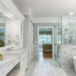 Klassisk inredning av ett en-suite badrum, med luckor med profilerade fronter, vita skåp, ett fristående badkar, en kantlös dusch, marmorkakel, grå väggar, marmorgolv, ett undermonterad handfat, marmorbänkskiva, grått golv och dusch med gångjärnsdörr