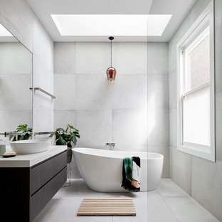 Photo of a mid-sized contemporary master bathroom in Melbourne with flat-panel cabinets, dark wood cabinets, a freestanding tub, gray tile, engineered quartz benchtops, grey floor, an open shower, a curbless shower and a vessel sink.