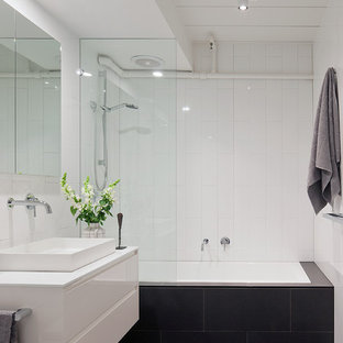 Design ideas for a mid-sized contemporary bathroom in Melbourne with white cabinets, a drop-in tub, a shower/bathtub combo, white walls, flat-panel cabinets, white tile, ceramic tile and a vessel sink.