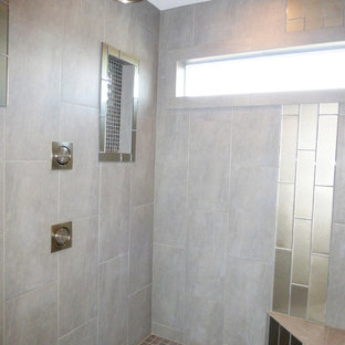 Ejemplo de cuarto de baño principal, actual, grande, con lavabo bajoencimera, armarios con paneles con relieve, puertas de armario de madera en tonos medios, encimera de granito, bañera encastrada, ducha empotrada, sanitario de dos piezas, baldosas y/o azulejos grises, baldosas y/o azulejos de vidrio laminado, paredes grises y suelo de baldosas de porcelana