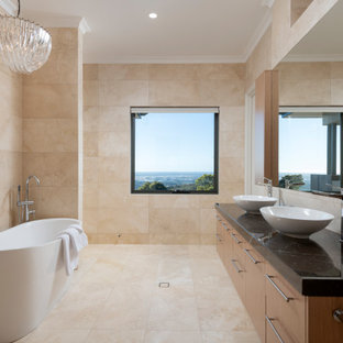 Expansive contemporary master bathroom in Perth with recessed-panel cabinets, light wood cabinets, a freestanding tub, a double shower, beige tile, travertine, beige walls, travertine floors, a vessel sink, engineered quartz benchtops, beige floor and brown benchtops.
