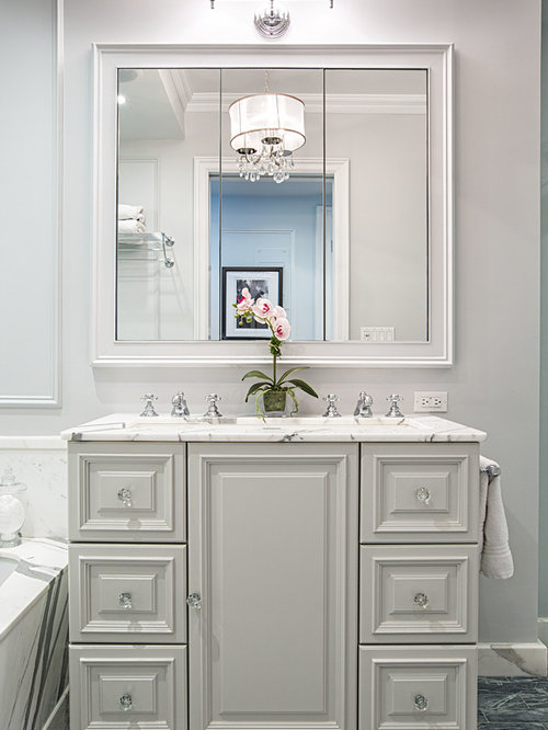 Example Of A Classic Bathroom Design In New York With Raised Panel Cabinets  And White