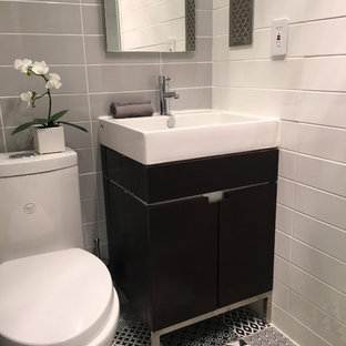 Inspiration for a small modern 3/4 white tile and ceramic tile cement tile floor and multicolored floor alcove shower remodel in New York with flat-panel cabinets, black cabinets, a one-piece toilet, gray walls, a console sink and a hinged shower door