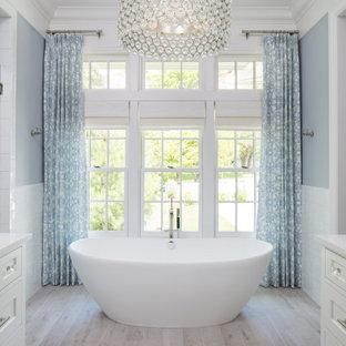 ミネアポリスの広いトランジショナルスタイルのおしゃれなマスターバスルーム (落し込みパネル扉のキャビネット、白いキャビネット、置き型浴槽、洗い場付きシャワー、一体型トイレ、白いタイル、青い壁、木目調タイルの床、アンダーカウンター洗面器、クオーツストーンの洗面台、グレーの床、開き戸のシャワー、白い洗面カウンター) の写真