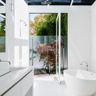 Esempio di una stanza da bagno padronale minimalista di medie dimensioni con ante lisce, ante bianche, doccia aperta, piastrelle bianche, piastrelle in pietra, pareti bianche, vasca freestanding, lavabo integrato, doccia aperta e pavimento bianco