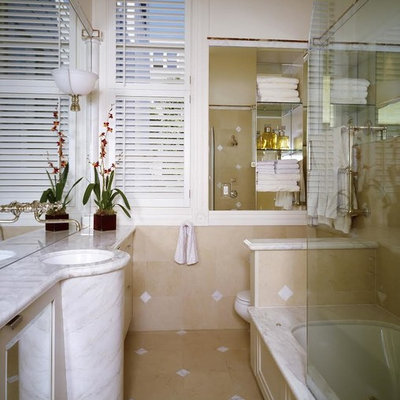 Example of a classic bathroom design in Other with marble countertops and an undermount tub