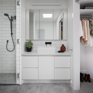 This is an example of a contemporary bathroom in Melbourne with flat-panel cabinets, white cabinets, white tile, subway tile, white walls, a vessel sink, grey floor and grey benchtops.