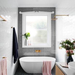 Свежая идея для дизайна: большая главная ванная комната в современном стиле с плоскими фасадами, фасадами цвета дерева среднего тона, отдельно стоящей ванной, открытым душем, серой плиткой, белой плиткой, плиткой кабанчик, настольной раковиной, открытым душем, раздельным унитазом, серыми стенами, полом из керамической плитки, столешницей из бетона, синим полом и серой столешницей - отличное фото интерьера