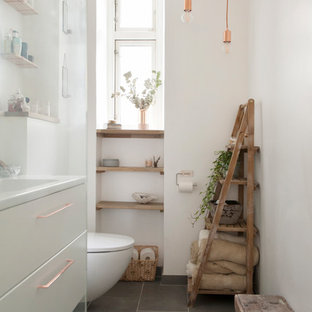 Inspiration for a scandinavian master gray floor bathroom remodel in Chicago with flat-panel cabinets, white cabinets, white walls, a wall-mount toilet and a console sink