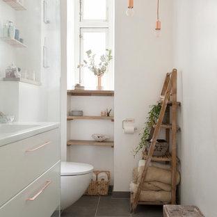 Esempio di una stanza da bagno padronale scandinava con ante lisce, ante bianche, pareti bianche, pavimento grigio, WC sospeso e lavabo a consolle