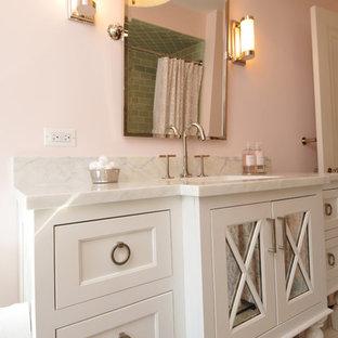 Modelo de cuarto de baño infantil, clásico, de tamaño medio, con armarios tipo mueble, puertas de armario blancas, bañera empotrada, combinación de ducha y bañera, sanitario de una pieza, baldosas y/o azulejos verdes, baldosas y/o azulejos de vidrio, paredes rosas, lavabo bajoencimera, encimera de mármol y suelo de baldosas de cerámica