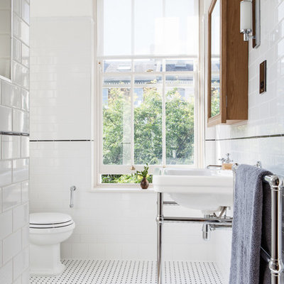 Ornate subway tile and black and white tile bathroom photo in London with a console sink, a two-piece toilet and white walls