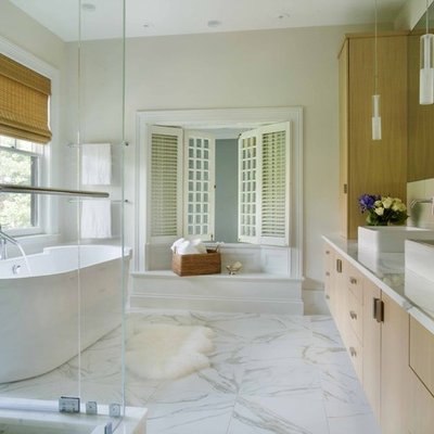 Trendy freestanding bathtub photo in Boston with marble countertops and a vessel sink