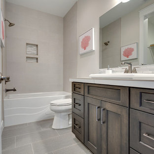 Large transitional master gray tile and porcelain tile porcelain tile bathroom photo in Portland with recessed-panel cabinets, dark wood cabinets, a two-piece toilet, gray walls, an undermount sink and tile countertops