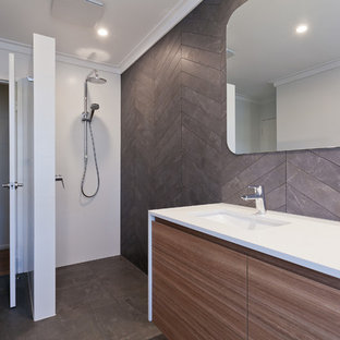 Inspiration for a mid-sized contemporary master bathroom in Perth with flat-panel cabinets, medium wood cabinets, an open shower, a two-piece toilet, gray tile, porcelain tile, white walls, porcelain floors, an undermount sink, engineered quartz benchtops, grey floor, an open shower and white benchtops.