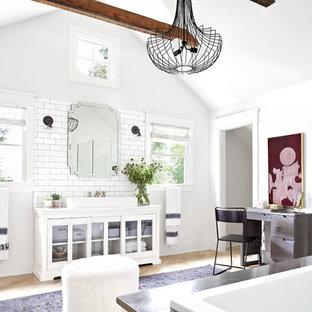 Diseño de cuarto de baño tradicional renovado con lavabo de seno grande, armarios tipo vitrina, puertas de armario blancas, bañera encastrada, ducha esquinera, baldosas y/o azulejos blancos, baldosas y/o azulejos de cemento, paredes blancas y suelo de madera en tonos medios