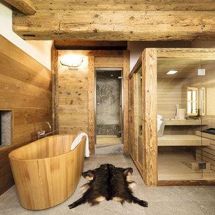 Новый формат декора квартиры: большая баня и сауна в стиле рустика с отдельно стоящей ванной, душевой комнатой, коричневыми стенами, полом из известняка, серым полом и душем с распашными дверями
