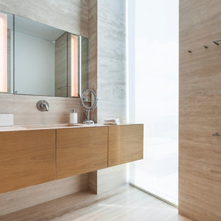 Mid-sized trendy 3/4 beige tile beige floor bathroom photo in Miami with flat-panel cabinets, medium tone wood cabinets, beige walls, an integrated sink, engineered quartz countertops, a hinged shower door and white countertops