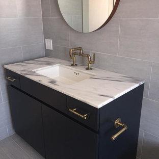 ボストンの中サイズのコンテンポラリースタイルのおしゃれなバスルーム (浴槽なし) (アンダーカウンター洗面器、大理石の洗面台、グレーのタイル、グレーの壁、オープンシェルフ、青いキャビネット、磁器タイル、クッションフロア、茶色い床) の写真