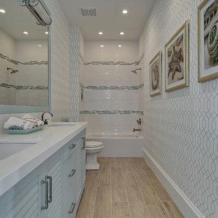 マイアミの大きいビーチスタイルのおしゃれな浴室 (ルーバー扉のキャビネット、青いキャビネット、アルコーブ型浴槽、シャワー付き浴槽、マルチカラーのタイル、磁器タイル、マルチカラーの壁、無垢フローリング、アンダーカウンター洗面器、珪岩の洗面台、茶色い床、シャワーカーテン、白い洗面カウンター) の写真