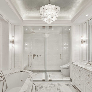 ニューヨークの広いトランジショナルスタイルのおしゃれなマスターバスルーム (インセット扉のキャビネット、白いキャビネット、アンダーマウント型浴槽、オープン型シャワー、白いタイル、モザイクタイル、白い壁、大理石の床、アンダーカウンター洗面器、大理石の洗面台、白い床、開き戸のシャワー、白い洗面カウンター、シャワーベンチ、洗面台2つ、造り付け洗面台、格子天井、パネル壁) の写真