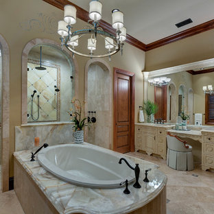 Photo of a large mediterranean ensuite bathroom in Orlando with freestanding cabinets, white cabinets, a built-in bath, a double shower, beige tiles, travertine tiles, beige walls, travertine flooring, a submerged sink, onyx worktops, beige floors and an open shower.