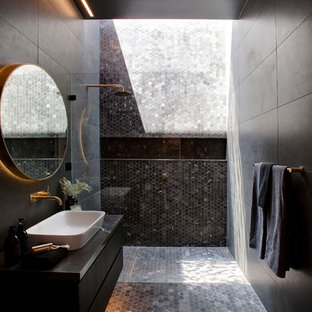 Inspiration for a contemporary 3/4 bathroom in Sydney with flat-panel cabinets, black cabinets, an alcove shower, black tile, gray tile, black walls, mosaic tile floors, a vessel sink, black floor and an open shower.
