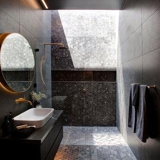 シドニーのコンテンポラリースタイルのおしゃれなバスルーム (浴槽なし) (フラットパネル扉のキャビネット、黒いキャビネット、アルコーブ型シャワー、黒いタイル、グレーのタイル、黒い壁、モザイクタイル、ベッセル式洗面器、黒い床、オープンシャワー) の写真
