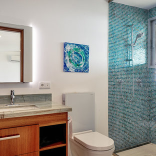 Doorless shower - mid-sized modern master blue tile and mosaic tile doorless shower idea in Miami with flat-panel cabinets, medium tone wood cabinets, a wall-mount toilet, white walls, an undermount sink, granite countertops and green countertops