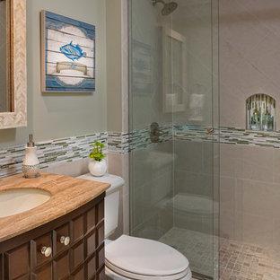 Immagine di una stanza da bagno stile marino con lavabo sottopiano, ante con bugna sagomata, ante in legno bruno, doccia alcova, WC a due pezzi, piastrelle a listelli, pareti verdi, piastrelle grigie e top marrone