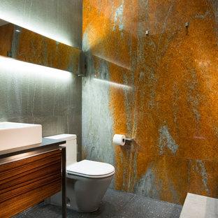 Imagen de cuarto de baño con ducha, contemporáneo, pequeño, con armarios con paneles lisos, puertas de armario de madera oscura, baldosas y/o azulejos verdes, baldosas y/o azulejos naranja, paredes verdes, lavabo sobreencimera, suelo gris, encimeras negras y sanitario de una pieza
