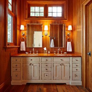 Modelo de cuarto de baño principal, rural, grande, con lavabo bajoencimera, armarios tipo mueble, puertas de armario con efecto envejecido, encimera de madera y suelo de madera en tonos medios