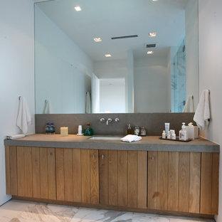 Foto de cuarto de baño con ducha, moderno, de tamaño medio, con puertas de armario de madera oscura, baldosas y/o azulejos blancos, suelo de mármol, armarios con paneles lisos, baldosas y/o azulejos de piedra, paredes blancas, encimera de piedra caliza, lavabo bajoencimera, suelo gris y encimeras grises