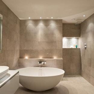 Diseño de cuarto de baño actual con lavabo sobreencimera, armarios con paneles lisos, puertas de armario blancas, bañera exenta, baldosas y/o azulejos beige, paredes beige y ducha a ras de suelo
