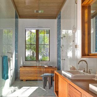 Ejemplo de cuarto de baño exótico con armarios con paneles lisos, lavabo sobreencimera, puertas de armario de madera oscura, encimera de madera, bañera exenta, ducha empotrada, baldosas y/o azulejos azules y encimeras marrones
