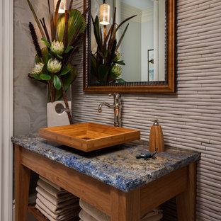 Tropisches Badezimmer mit Aufsatzwaschbecken, hellbraunen Holzschränken, beigefarbenen Fliesen, grauer Wandfarbe, Kiesel-Bodenfliesen, offenen Schränken und blauer Waschtischplatte in Miami