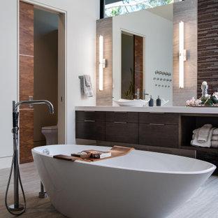Неиссякаемый источник вдохновения для домашнего уюта: огромная главная ванная комната в современном стиле с плоскими фасадами, темными деревянными фасадами, гидромассажной ванной, унитазом-моноблоком, белыми стенами, полом из керамогранита, настольной раковиной, серым полом, белой столешницей, тумбой под две раковины и подвесной тумбой