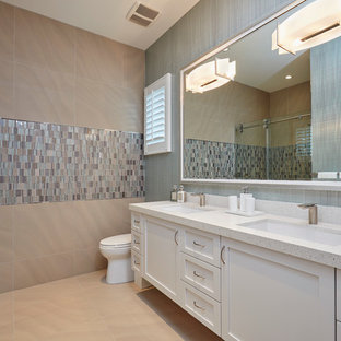 This is an example of a large contemporary master bathroom in Miami with recessed-panel cabinets, white cabinets, a drop-in tub, an open shower, beige walls, ceramic floors, an undermount sink, terrazzo benchtops, beige floor and a sliding shower screen.
