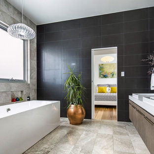 This is an example of a large contemporary shower room in Adelaide with freestanding cabinets, white cabinets, a freestanding bath, a one-piece toilet, brown walls, travertine flooring, black tiles, travertine tiles, quartz worktops, brown floors and green worktops.