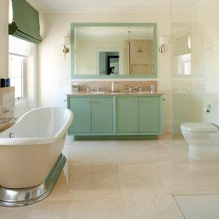 Idée de décoration pour une salle de bain tradition avec une baignoire indépendante, un placard à porte plane, des portes de placards vertess et un sol beige.
