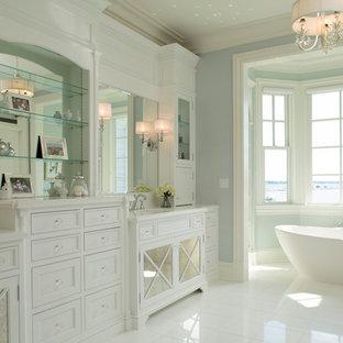 Foto de cuarto de baño principal, tradicional, extra grande, con armarios tipo mueble, puertas de armario blancas, bañera exenta, baldosas y/o azulejos blancos, paredes azules y encimera de granito