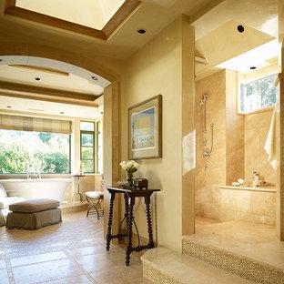 Diseño de cuarto de baño mediterráneo con bañera exenta y paredes beige